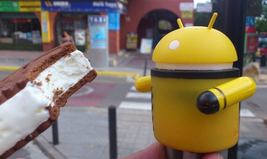 Žuti android jede ice cream sandwich od čokolade